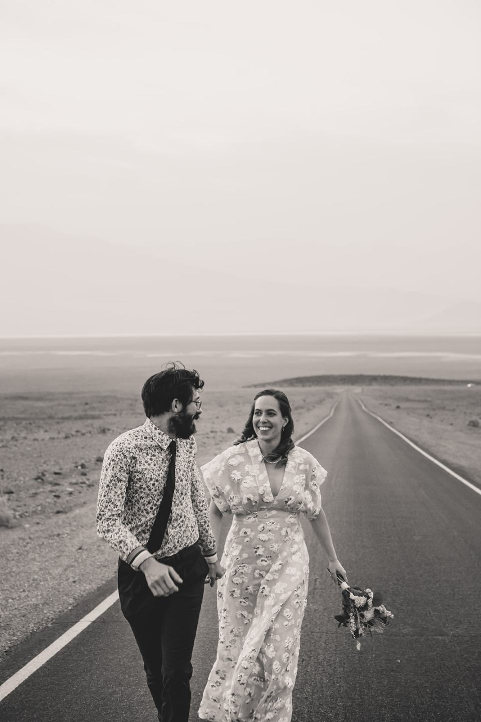 bride and groom run on road at Artist Palette