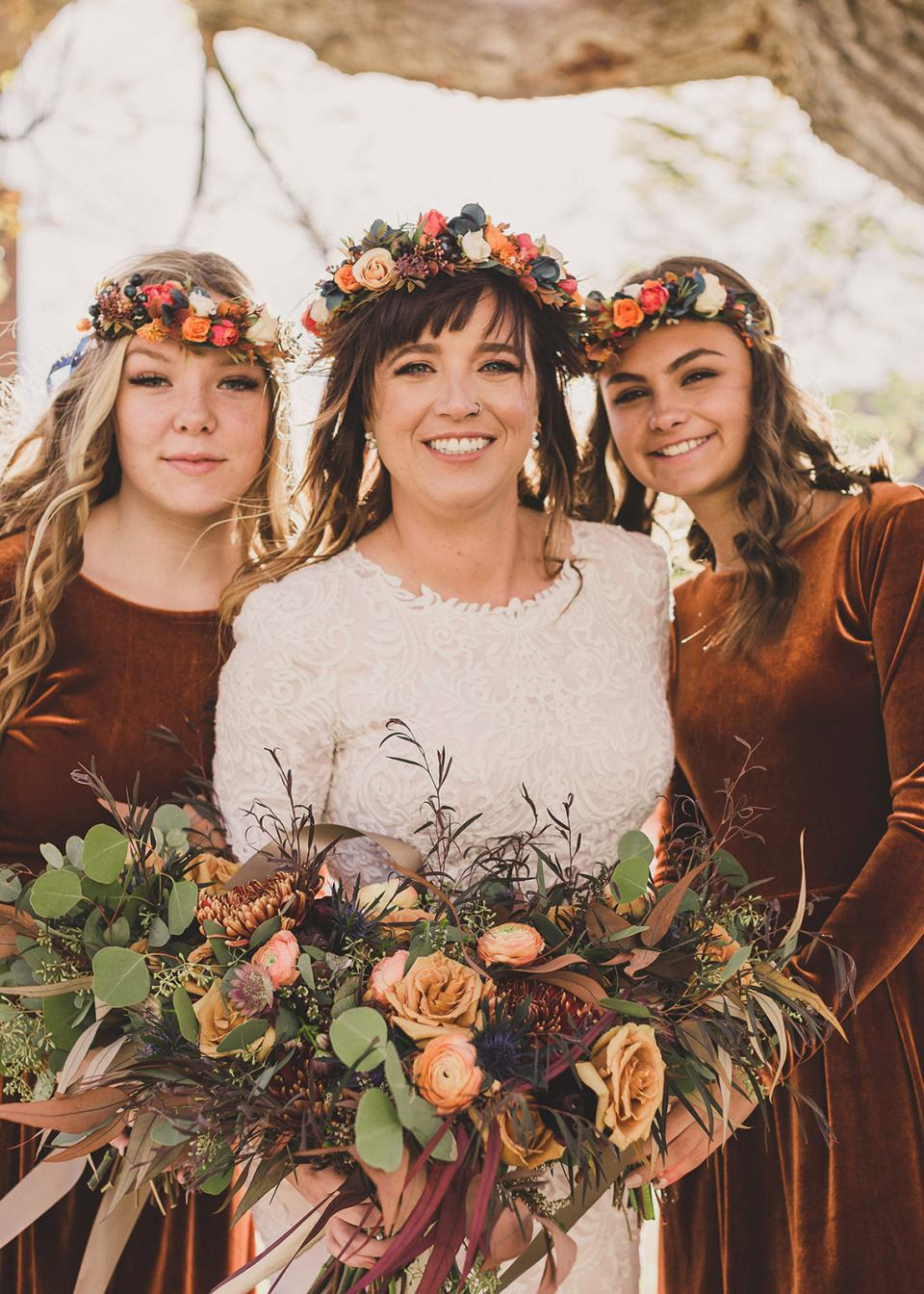 bride poses with two daughters in rust gowns with flower crowns