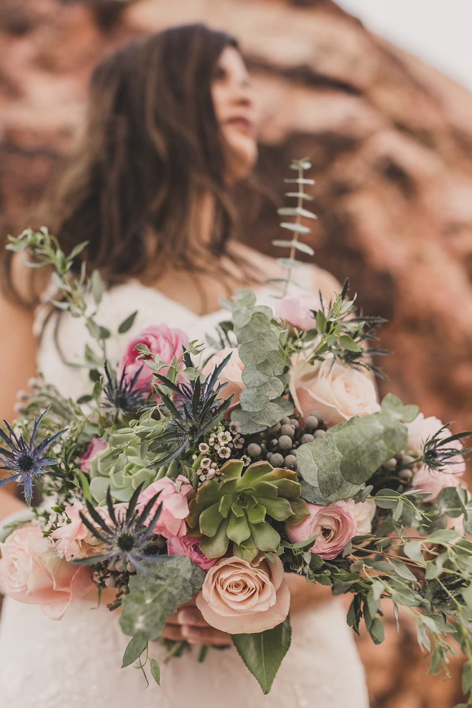 bride holds bouquet of succulents and pink flowers