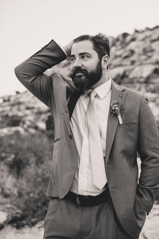 groom brushes back hair during portraits in Las Vegas
