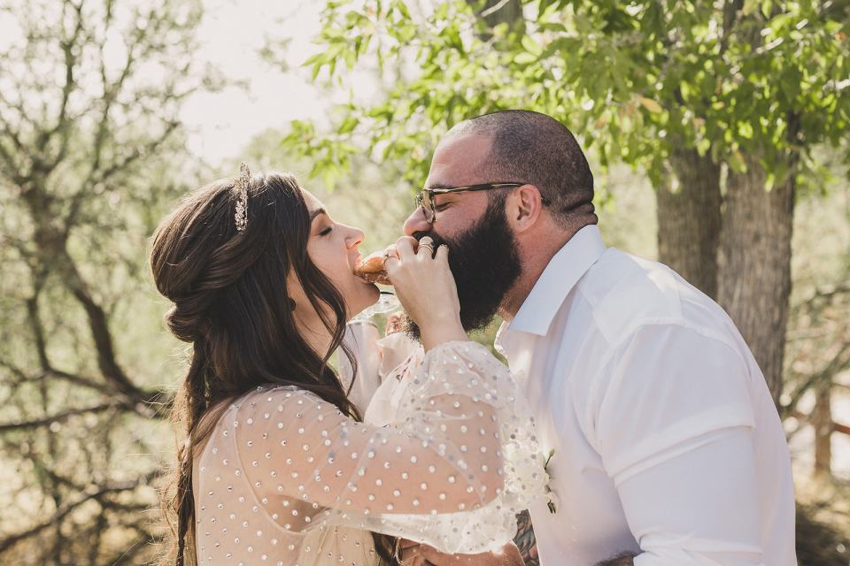 bride and groom bite donut during elopement reception