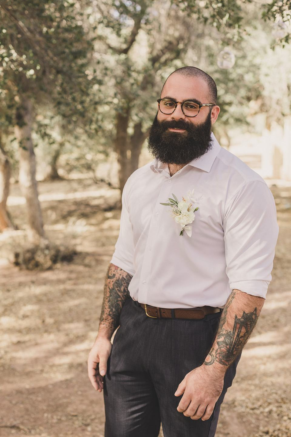 groom poses in button up shirt with boutineere