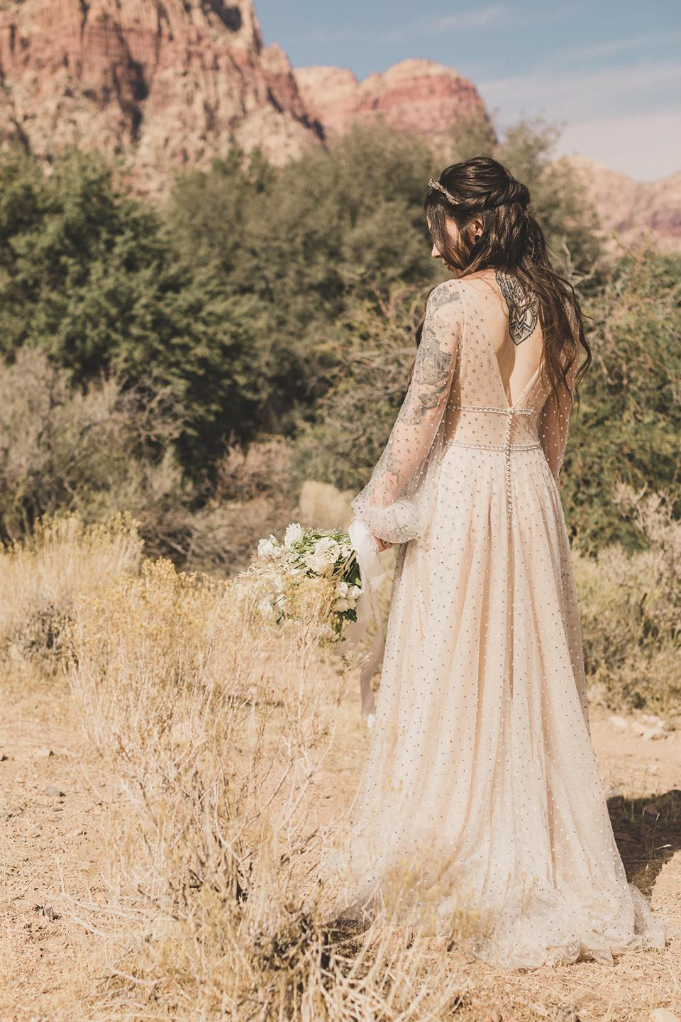 bride shows off back of vintage wedding gown