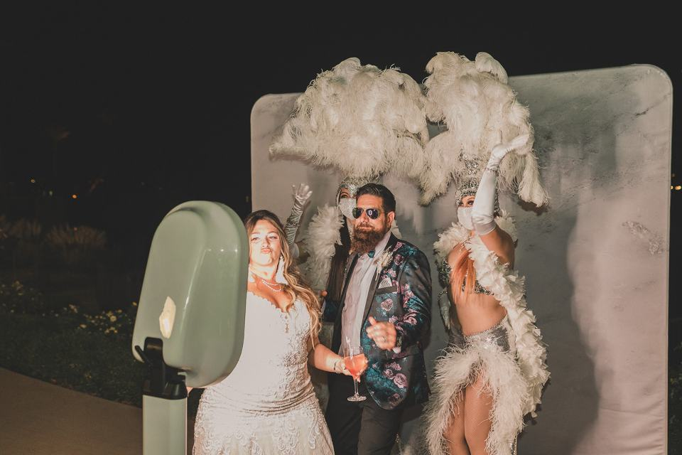 bride and groom pose with showgirls at photo booth