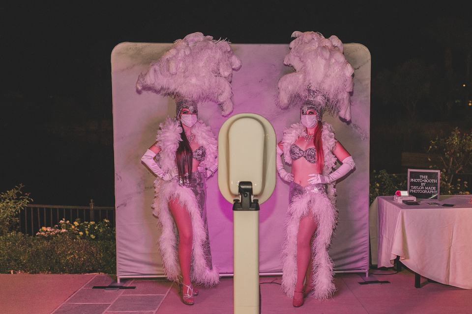 showgirls pose by photo booth for The Westin Lake Las Vegas wedding reception
