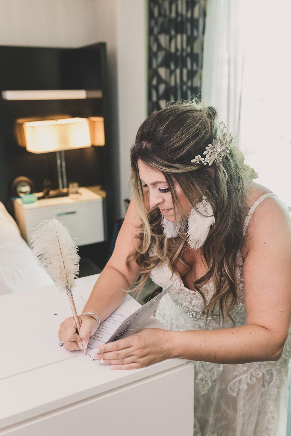 bride writes groom a letter with feather pen