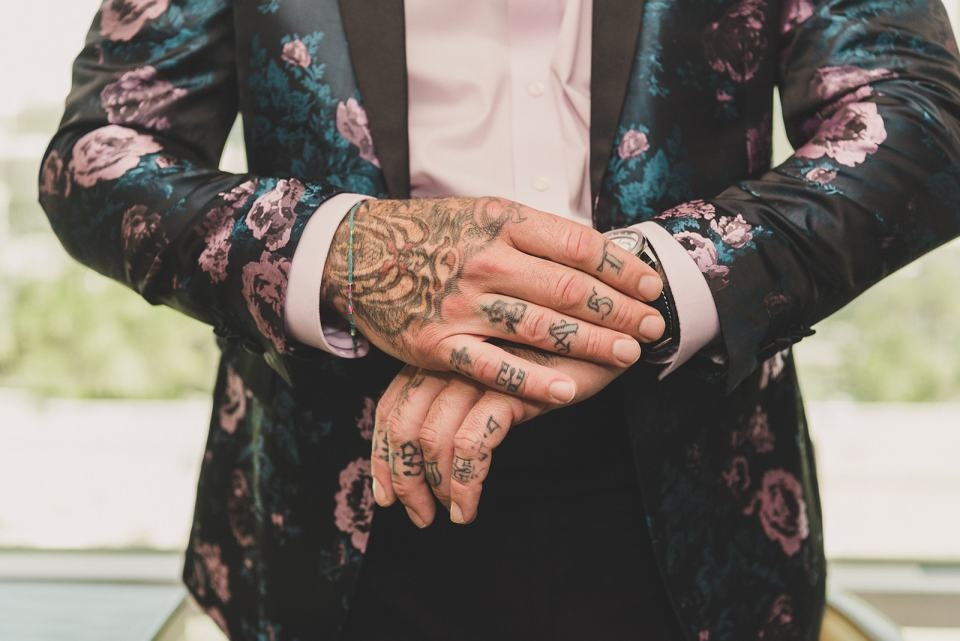 groom with hand tattoos adjusts watch before wedding