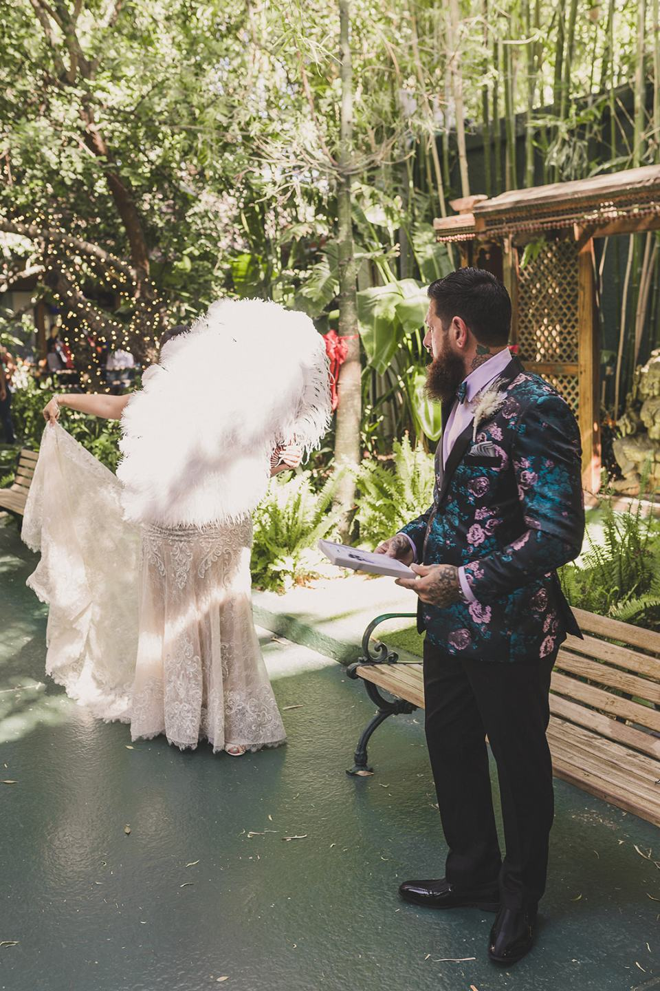 bride hides behind feather fan before first look