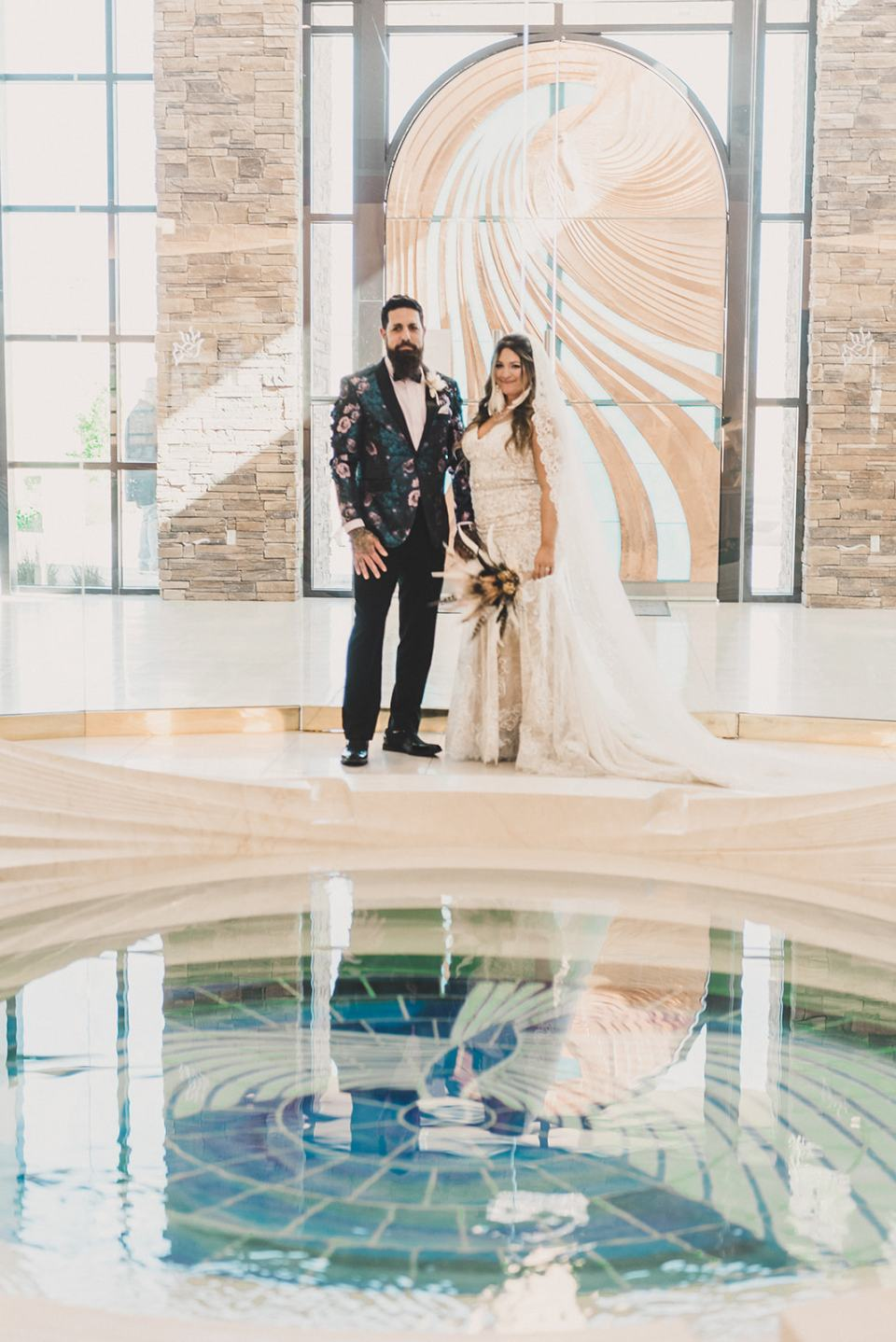 bride and groom pose by pond in Holy Spirit Roman Catholic Church
