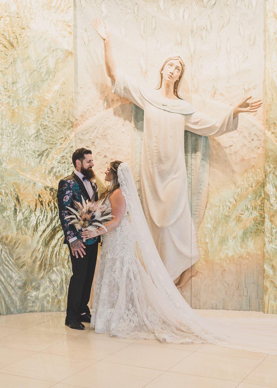 newlyweds pose by mural in Holy Spirit Roman Catholic Church