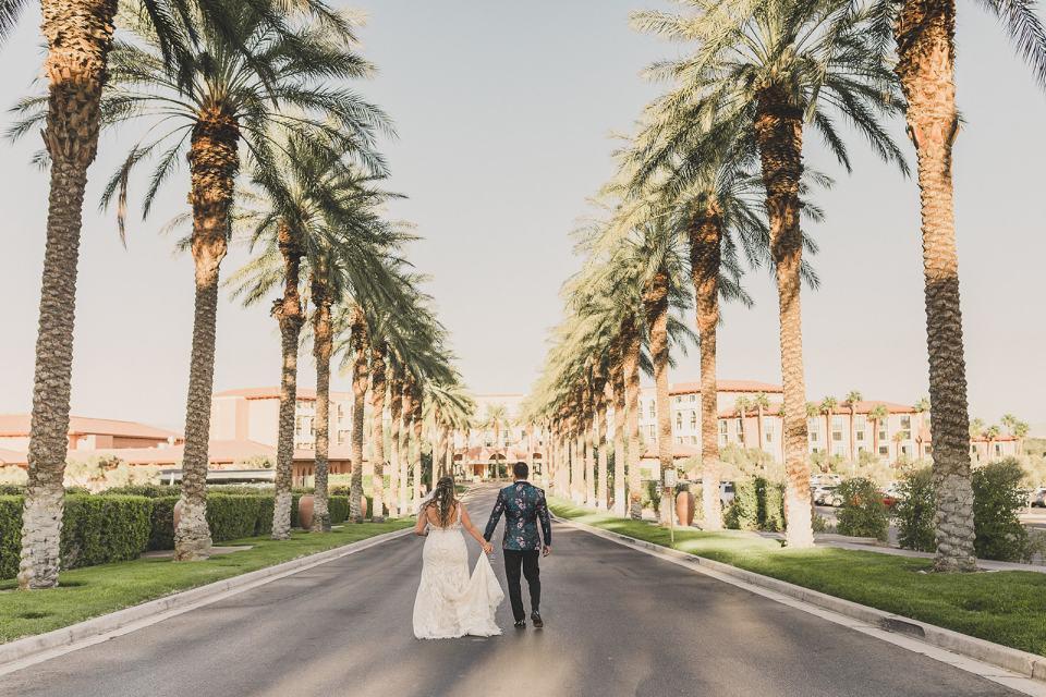 newlyweds walk on road with palm trees