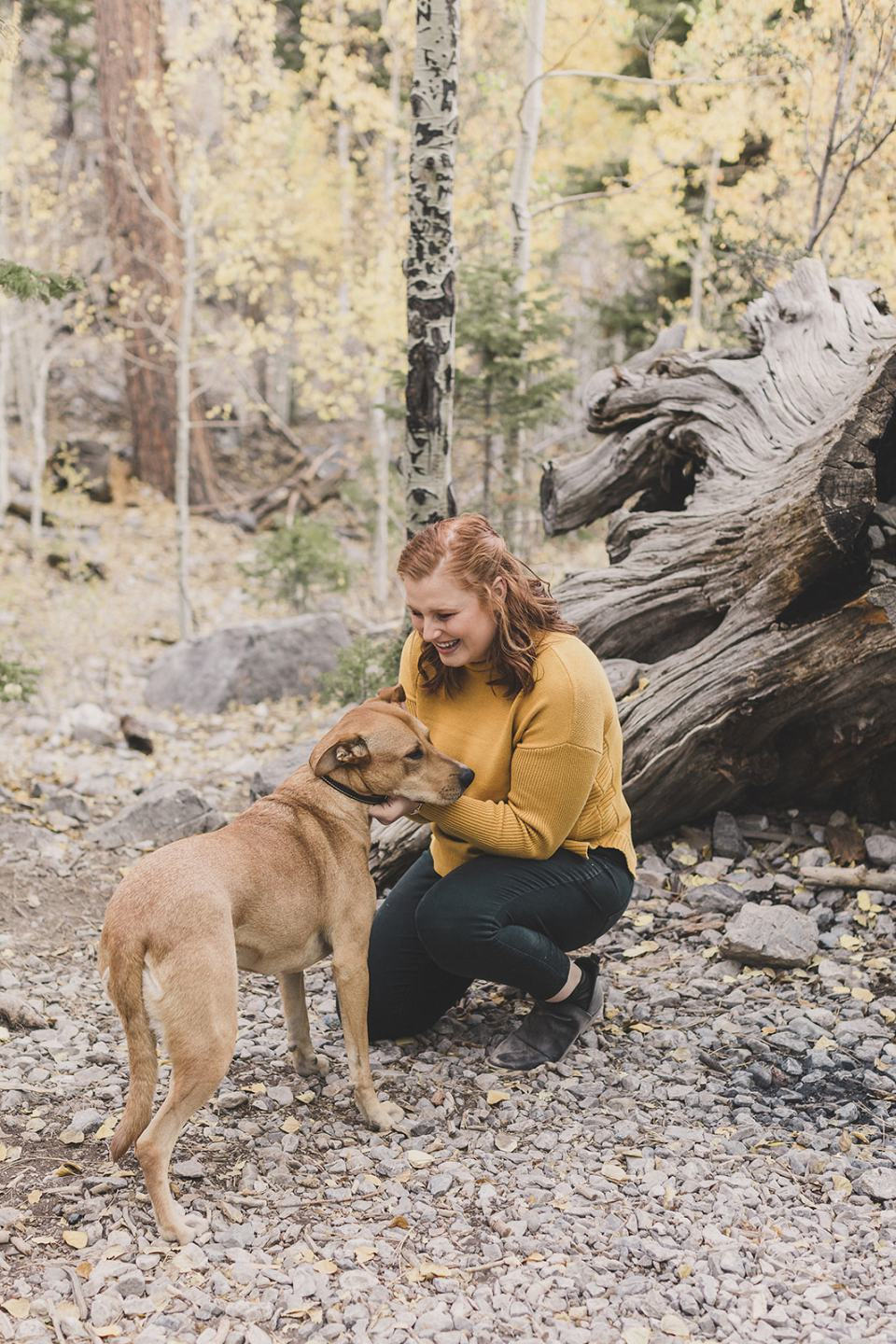 woman in mustard sweater plays with dog during family photos