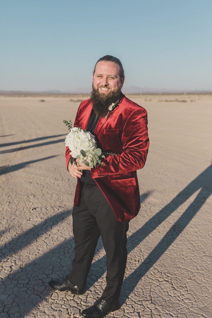 groom in red velvet suit jacket holds bride's bouquet