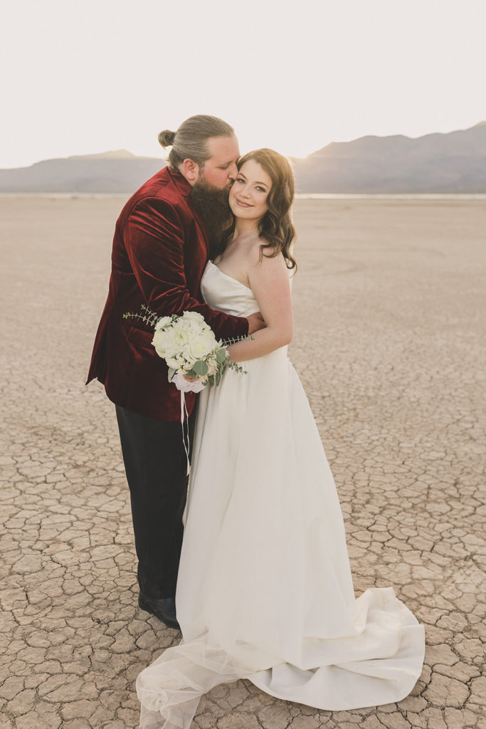bride and groom hug in desert after intimate wedding ceremony