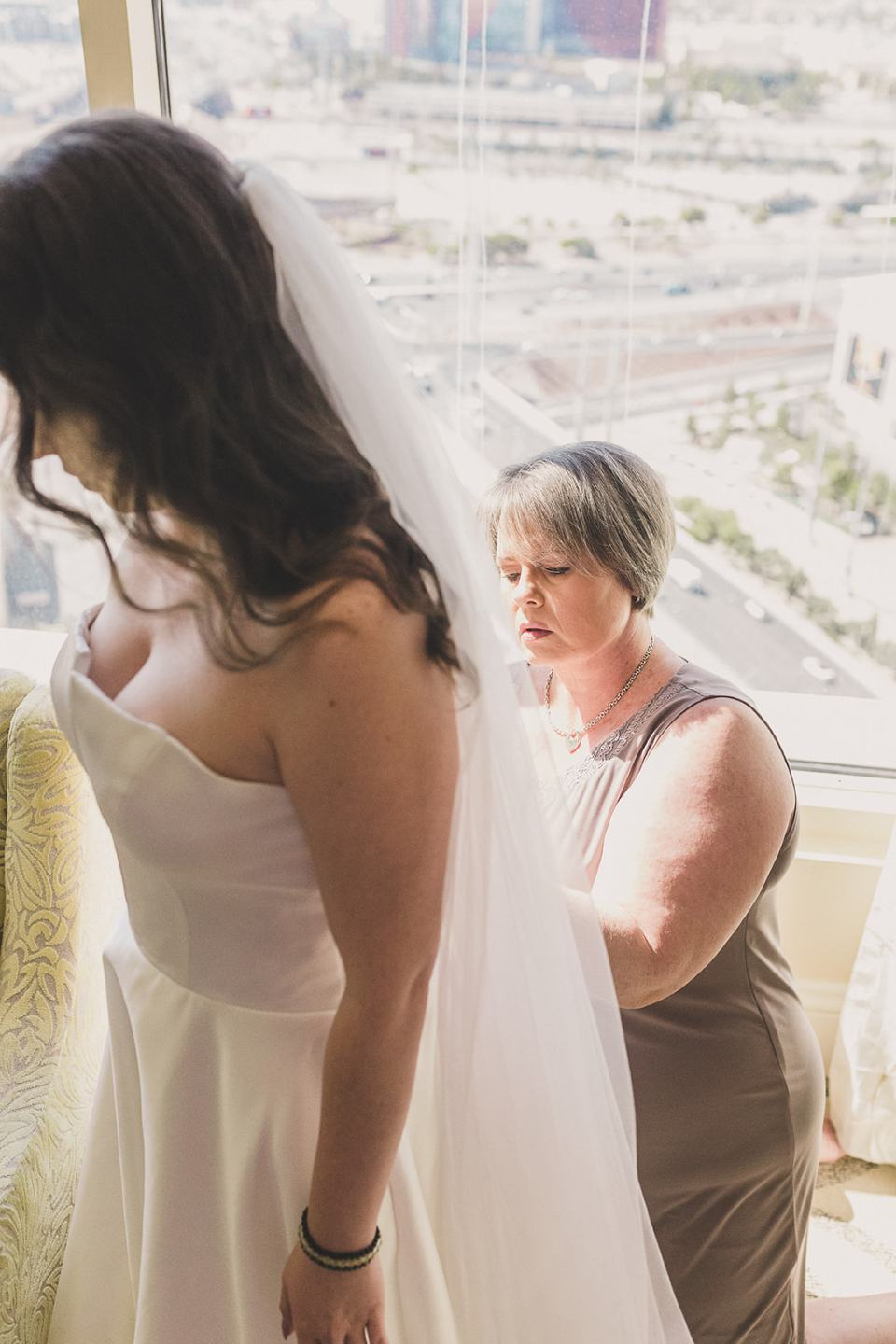 mother of the bride helps with gown