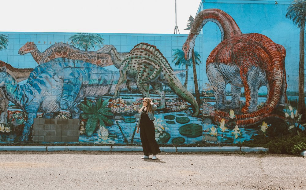 Taylor stands in front of a dinosaur mural in downtown Drumheller Alberta, Canada