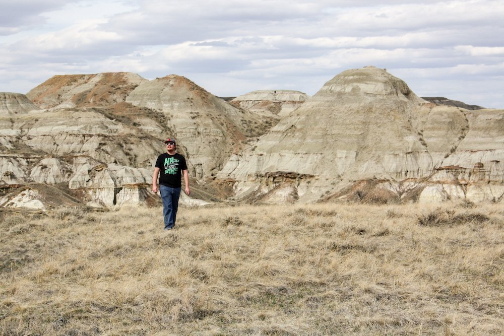 A man walks in front of hoodoos on the Trail of the Fossil Hunters at Dinosaur Provincial Park, Alberta