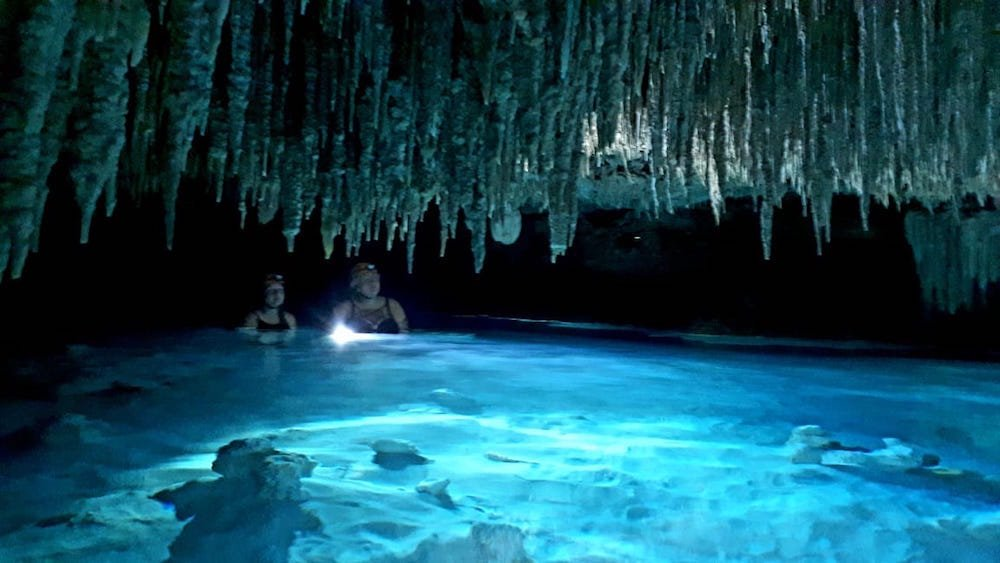 Taylor and a friend in water, standing under stalactites in a playa del carmen cave