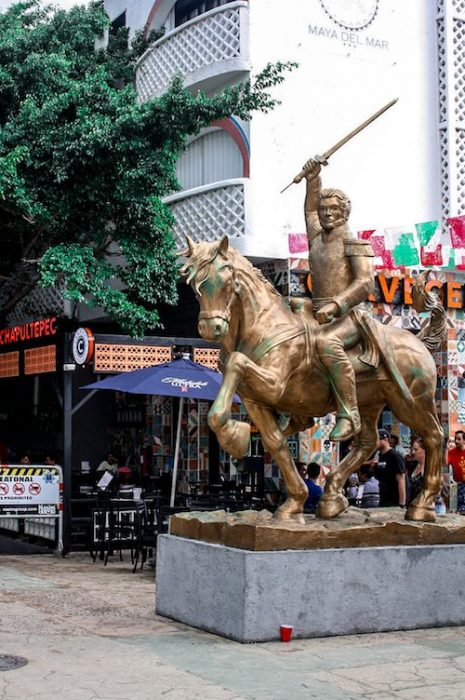 a statue of a man riding a horse in downtown playa del carmen
