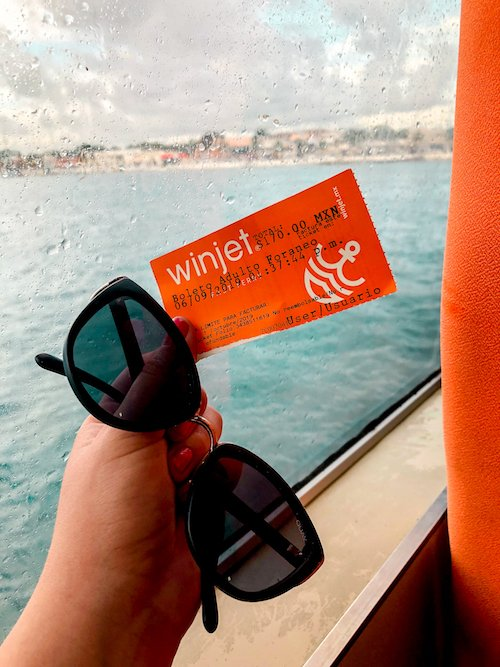 Winjet ticket and sunglasses in playa del carmen with the ocean in the background.