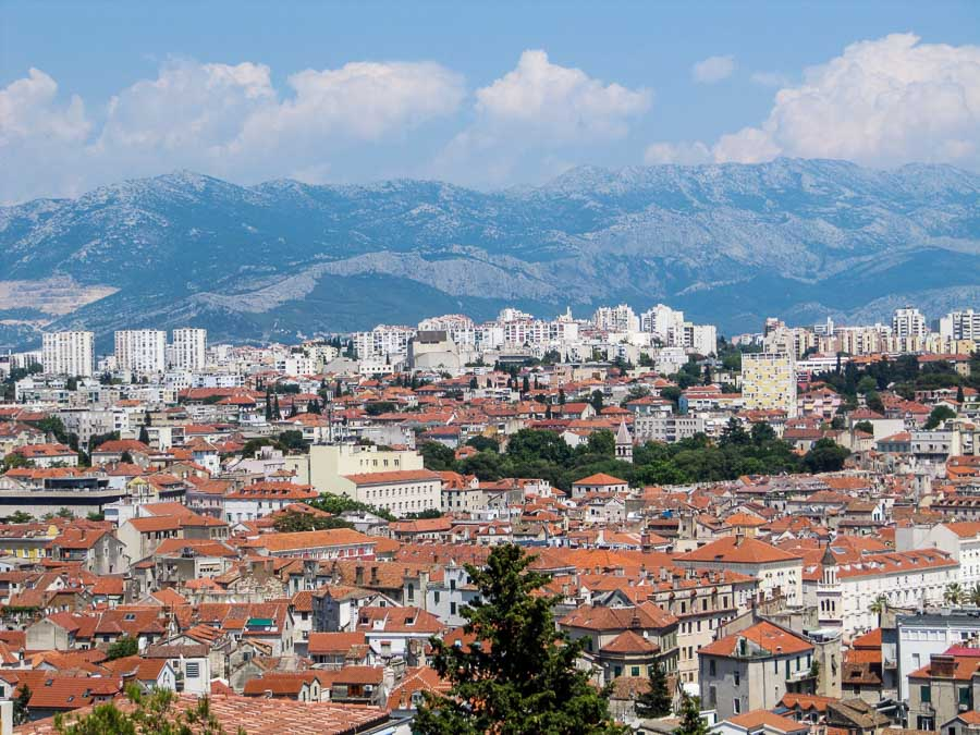An overhead shot of Split, Croatia with terracotta roofed buildings and mountains in the background
