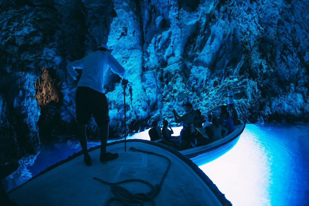 A man standing on a boat in the blue cave of Bisevo Island in Croatia