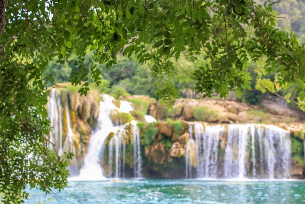View of a waterfall at krka national park in croatia with leaves in the foreground