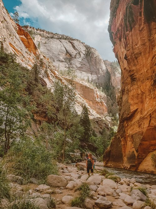 A woman stands in the middle of Zion Canyon in Zion National Park, Utah