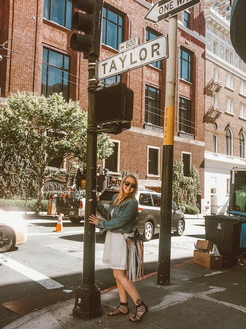 """Taylor stands in front of a sign that says """"Taylor"""" Street in San Francisco, California"""