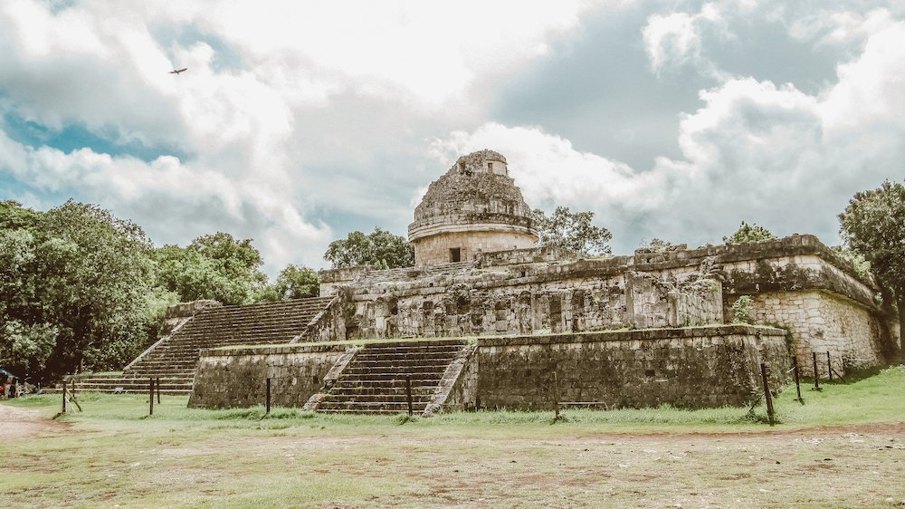 A bird flies over ancient ruins at the site of Chichen Itza, Mexico