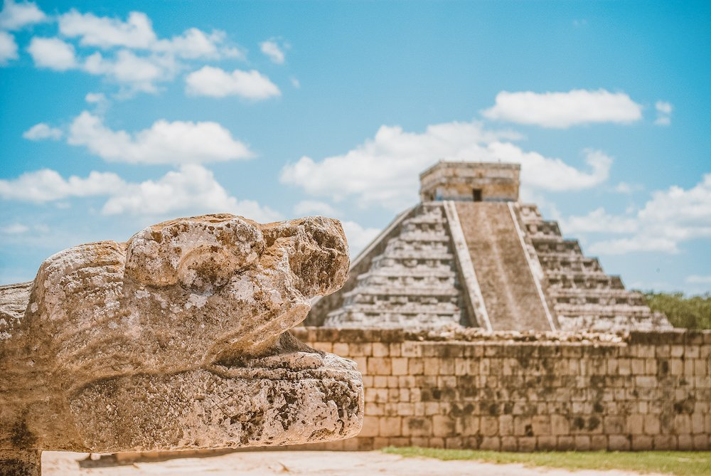 A pyramid at Chichen Itza is in the background while an ancient sculpted snake head is in the foreground