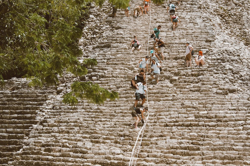 Visitors climb the coba ruins in quintana roo mexico, holding onto a rope as they go