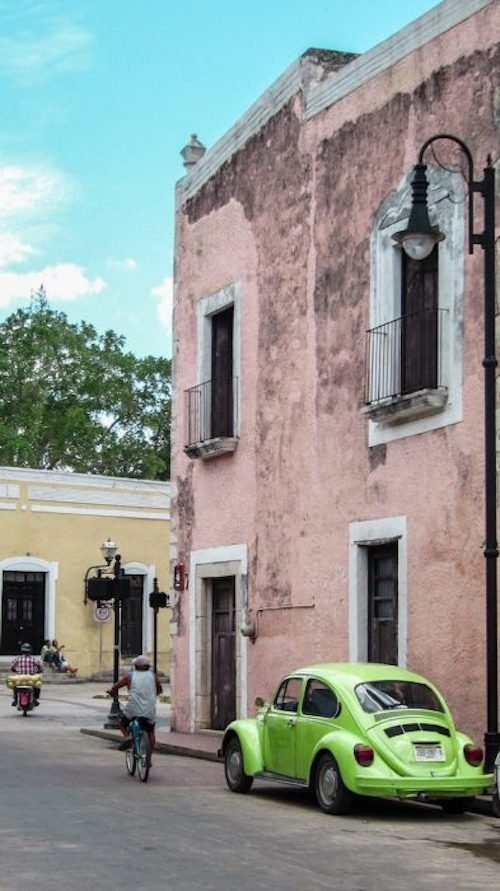 A green VW bug sits outside a pink building as a man rides a bicycle in Valladolid Mexico