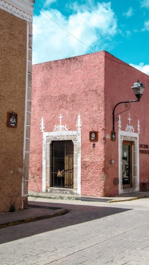 Pink and orange buildings against a bright blue sky in Valladolid Mexico