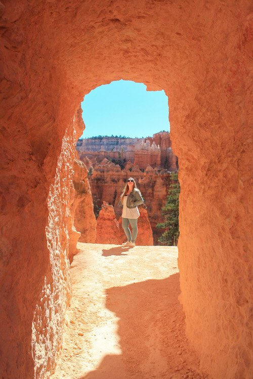 Taylor stands at the other side of a tunnel in Bryce Canyon National Park with hoodoos in the background