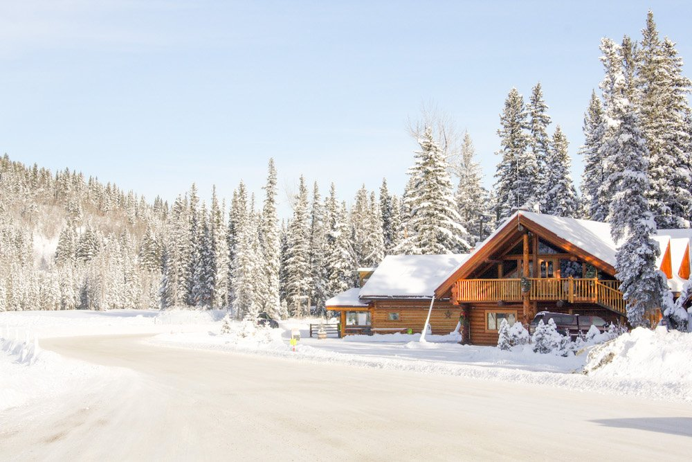 A wooden picturesque chalet is surrounded by snow-covered evergreen trees in Cochrane, Alberta
