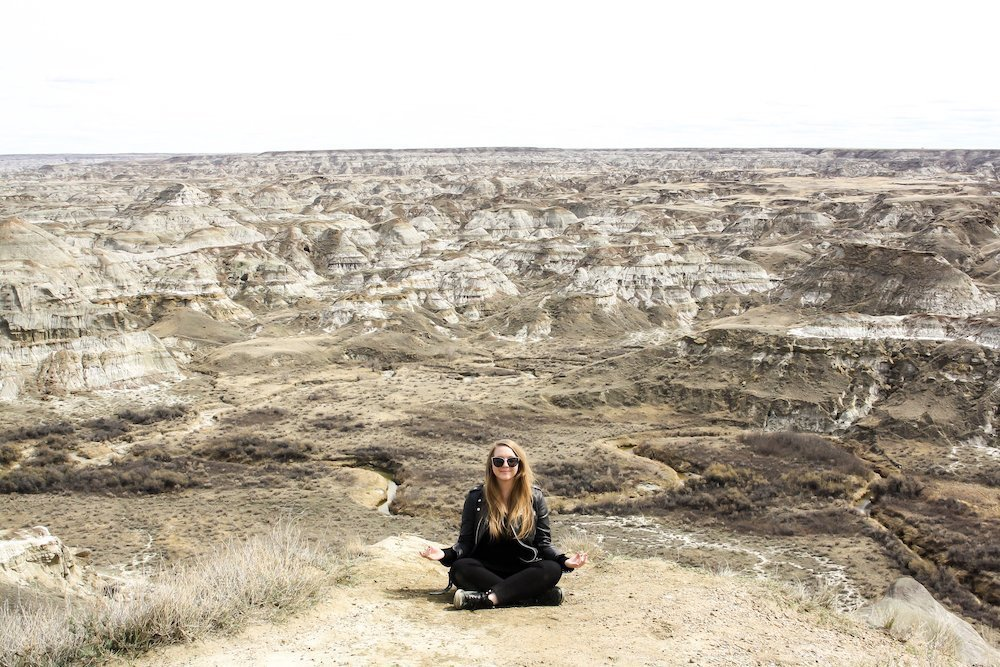 Taylor sits in front of a large valley coulee in Dinosaur Provincial Park, Alberta