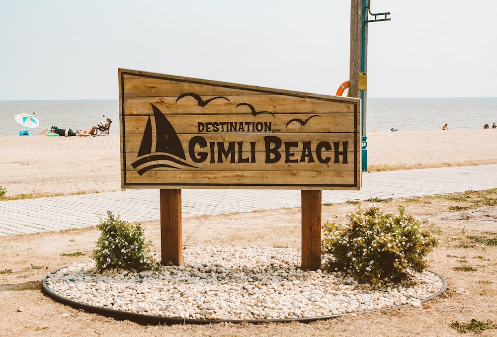 Gimli Beach sign, with the beach, lake, and sunbathers in the background