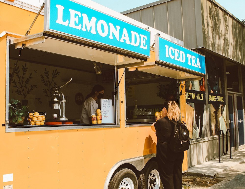 A woman buys a lemonade from a stand in Gimli, Manitoba
