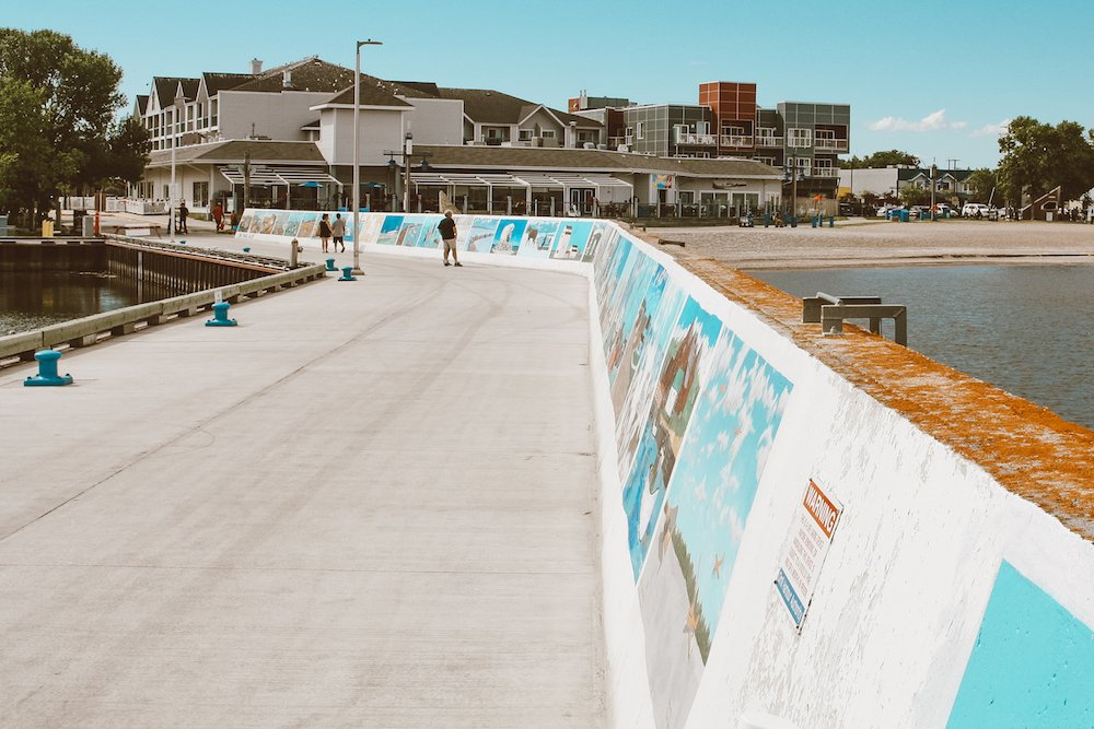 Gimli beach, boardwalk, and hotels with people checking out the murals in Manitoba