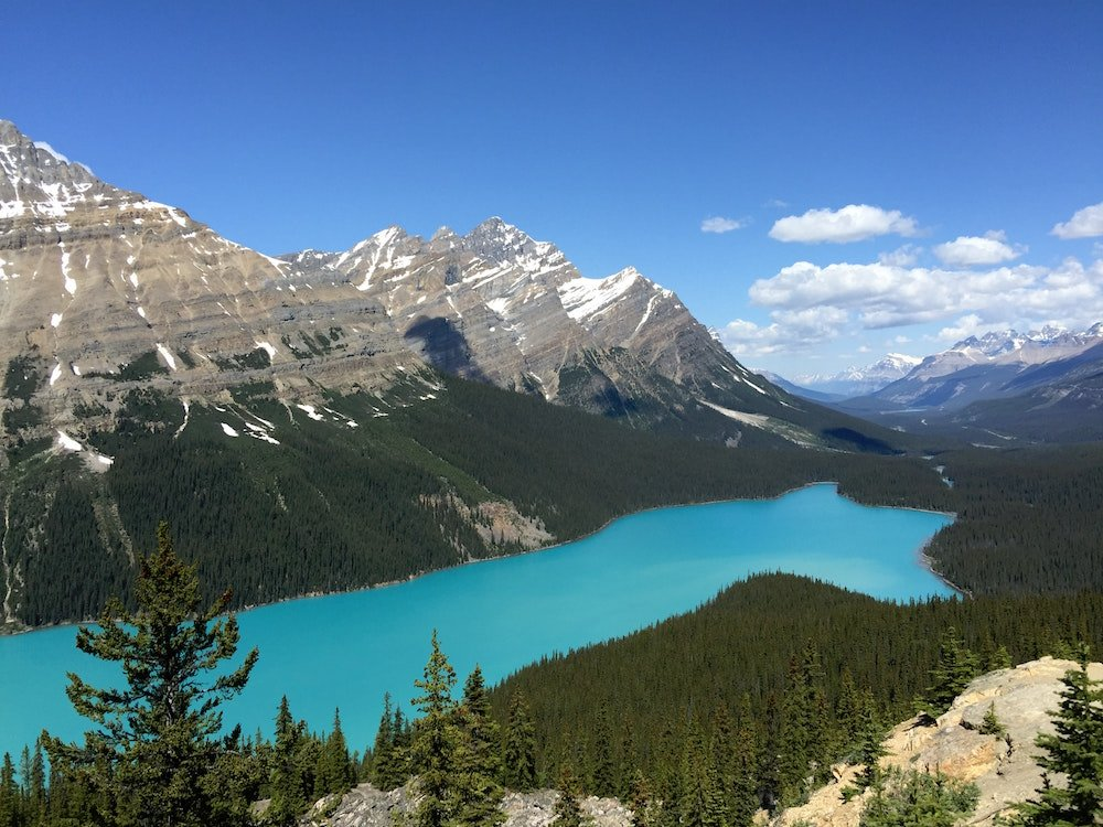 A turquoise lake is surrounded by rich alpine forests and towering mountains in Jasper National Park, Alberta