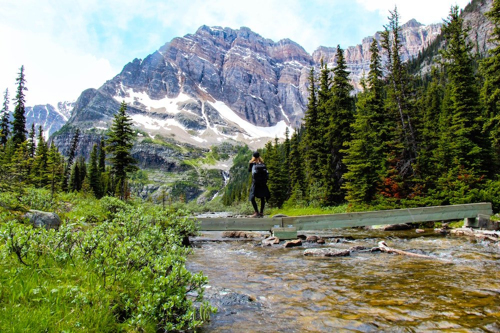 A woman stands on a small bridge in Kootenay National Park, in front of mountains and forests