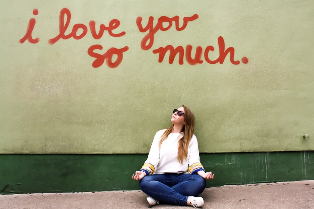 """Taylor sits in front of a wall that says """"I love you so much"""" in Austin, Texas"""