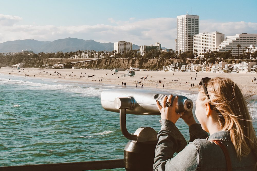 Taylor looks out over the ocean with a telescope in Los Angeles, California