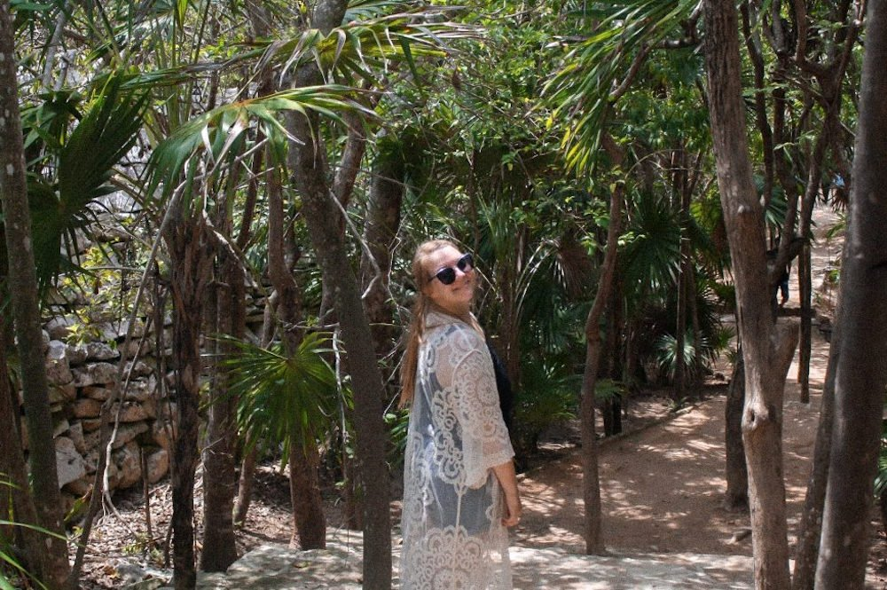 Taylor stands among pine trees and ruins in Tulum, Mexico