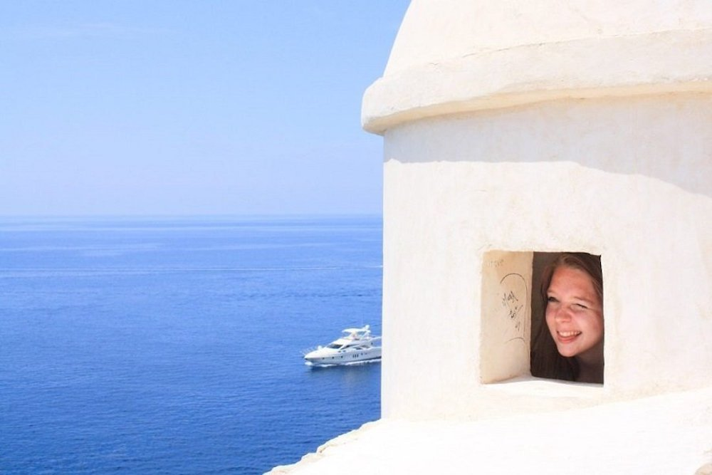Taylor looks out of a window over the Dalmatian Coast in Dubrovnik, Croatia. With a yacht in the background