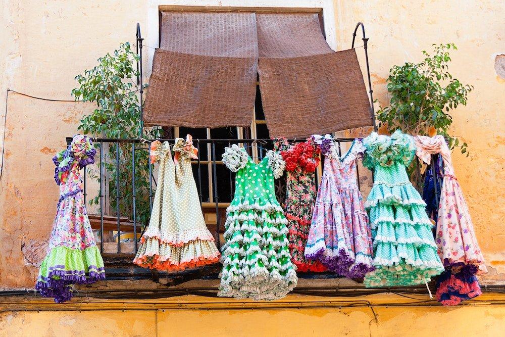 Flamenco dresses hang outside of a building in Granada, Spain
