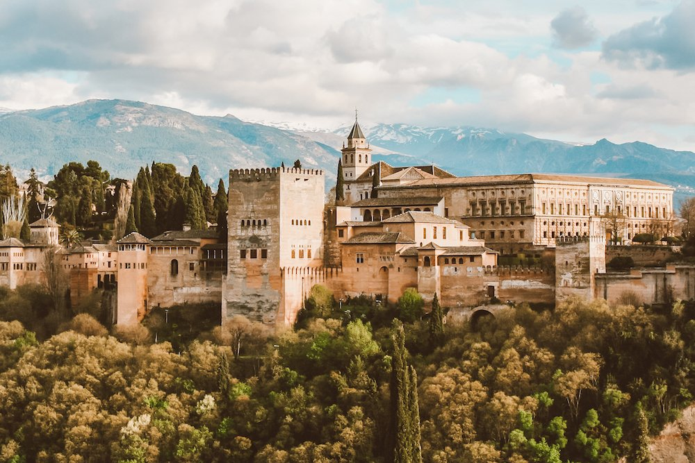 A photo of the alhambra palace in granada spain surrounded by trees