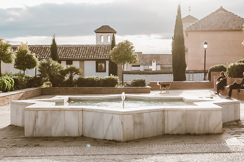 Two people play guitar in front of a water fountain as the sun sets in Granada, Spain