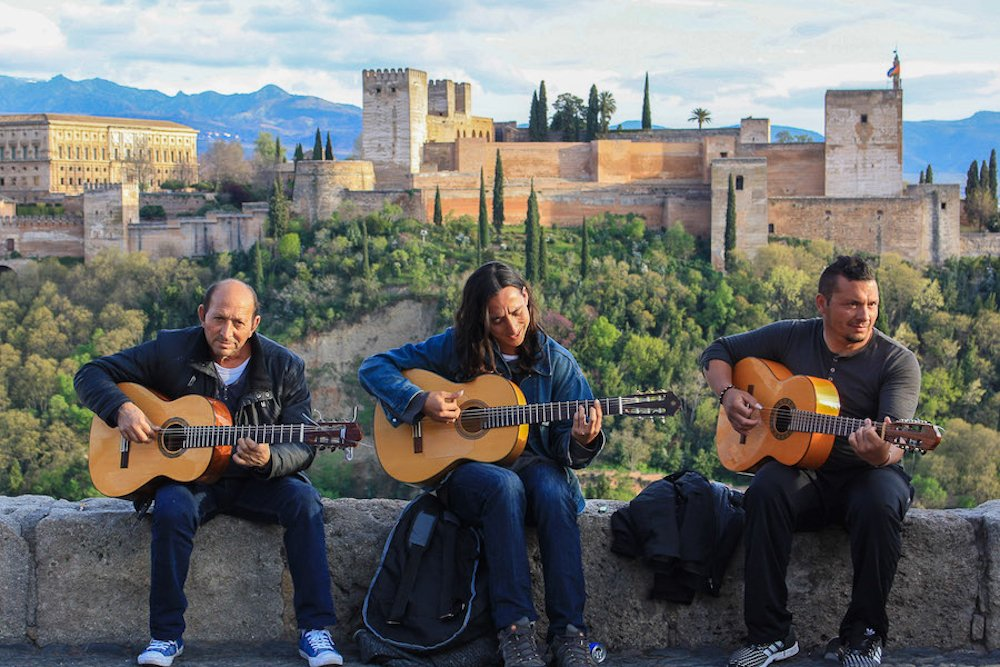 Three men play guitar at Mirador de San Nicolas in Granada, Spain